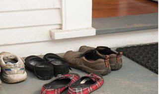Shoes for a family group outside a door