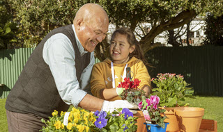 Father and daughter potting plants in the garden