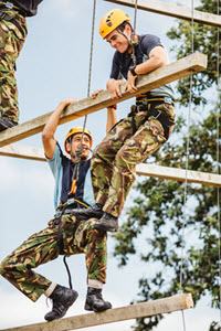 2 guys hanging off a wooden bar on a ropes course