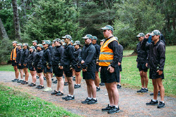 People standing in military lines in a forest at a LSV course